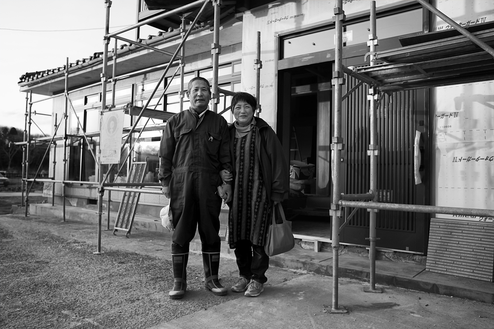 Watanabe-san and his wife pose for a photograph outside their home.