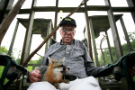 Bill Miles sits with the fox he rescued in an enclosure in the back yard of his home in near Pinckard, Ala.
