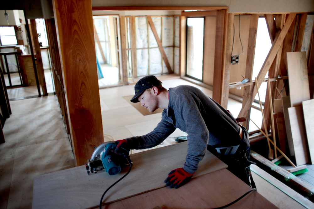 Carpenter Brandon Healey makes a cut to a piece of plywood in late March 2012.