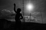 A young boy is silhouetted by the sun as he flies a kite on a beach community near Port-au-Price, Haiti.