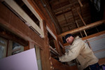 Volunteer Lynn Sedlbauer works to install a piece of drywall in a home damaged by the tsunami in Japan.