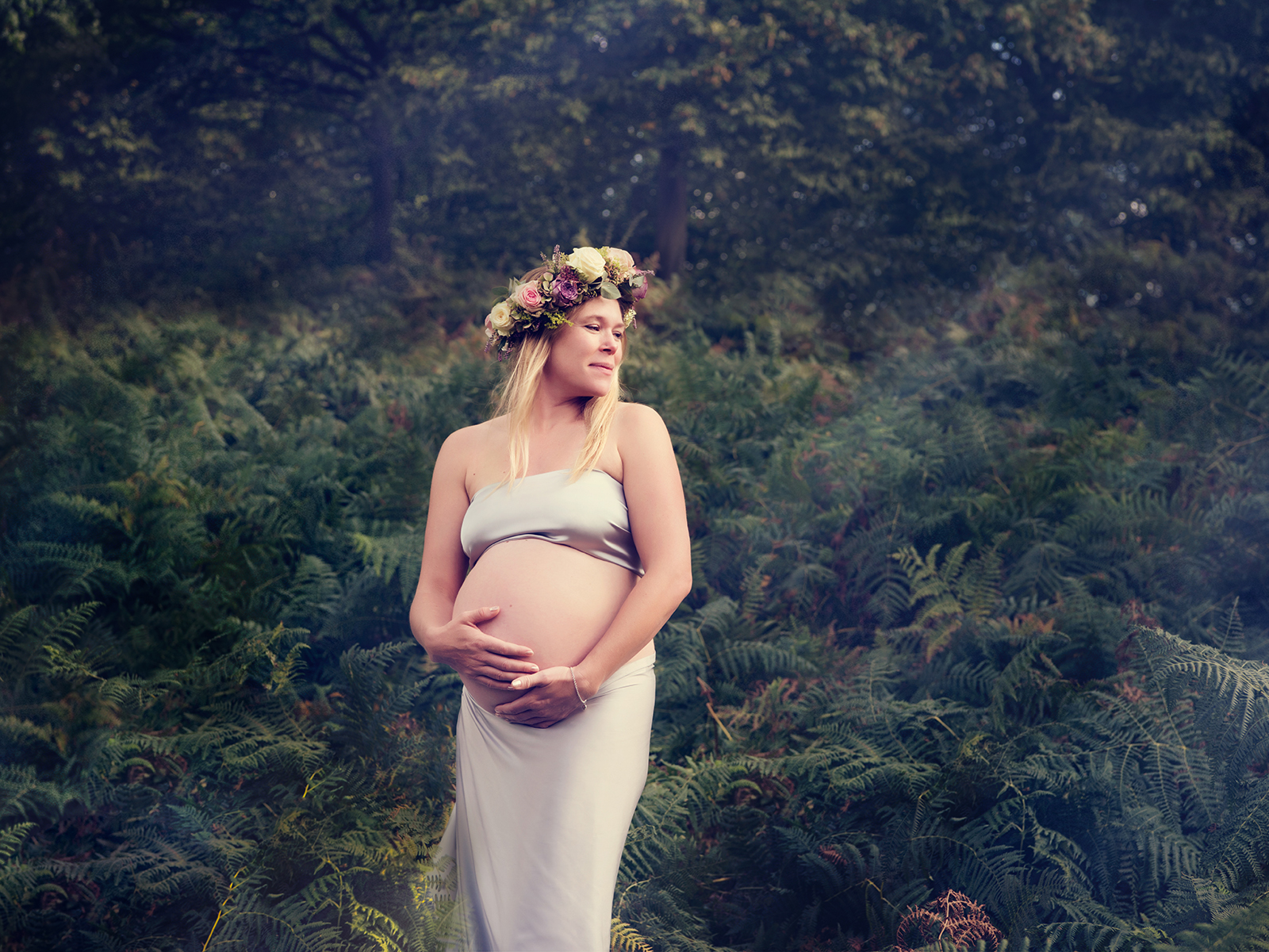 An outdoor maternity portrait of a mum-to-be wearing a flower crown and silky drapes.