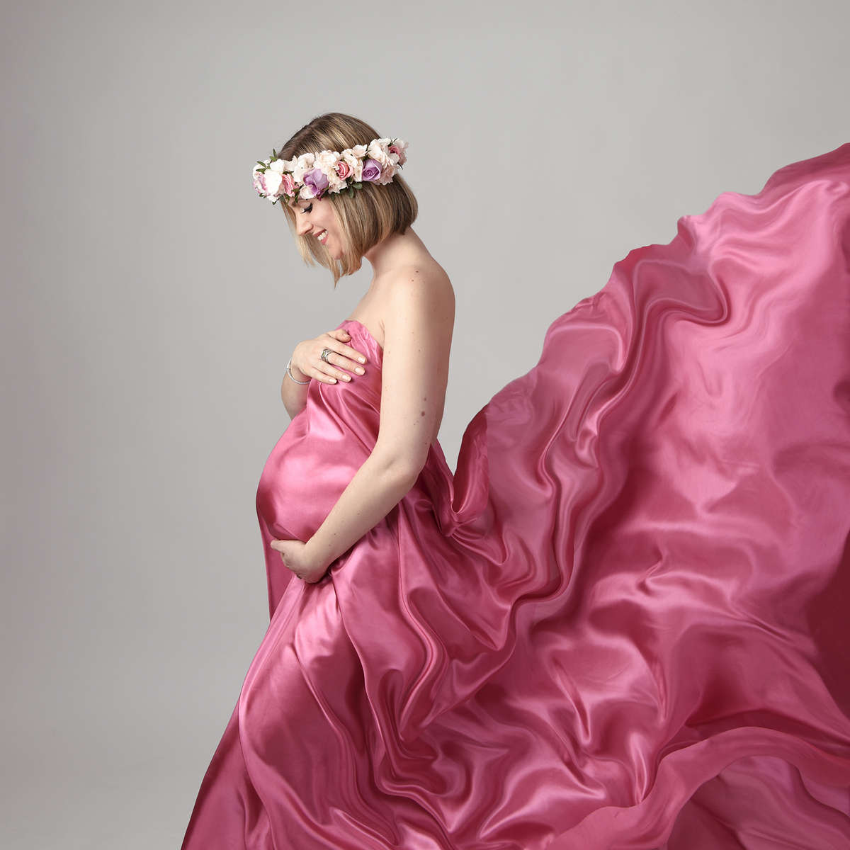 Colour maternity photograph of a pregnant woman standing holding her tummy with flowing  red silk. London's best maternity photographer.