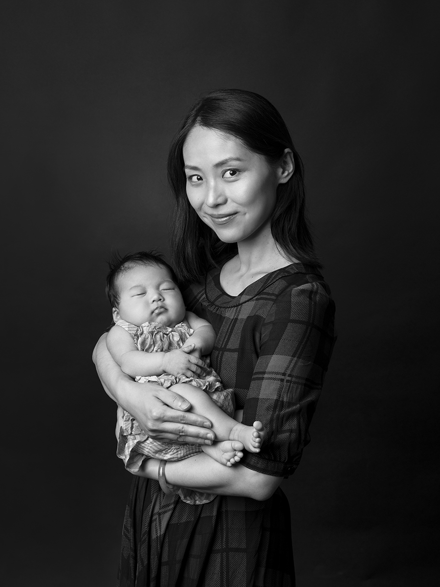 Black and white photograph of a Mum holding her new born baby close to her chest in her arms. Taken against a black backdrop.