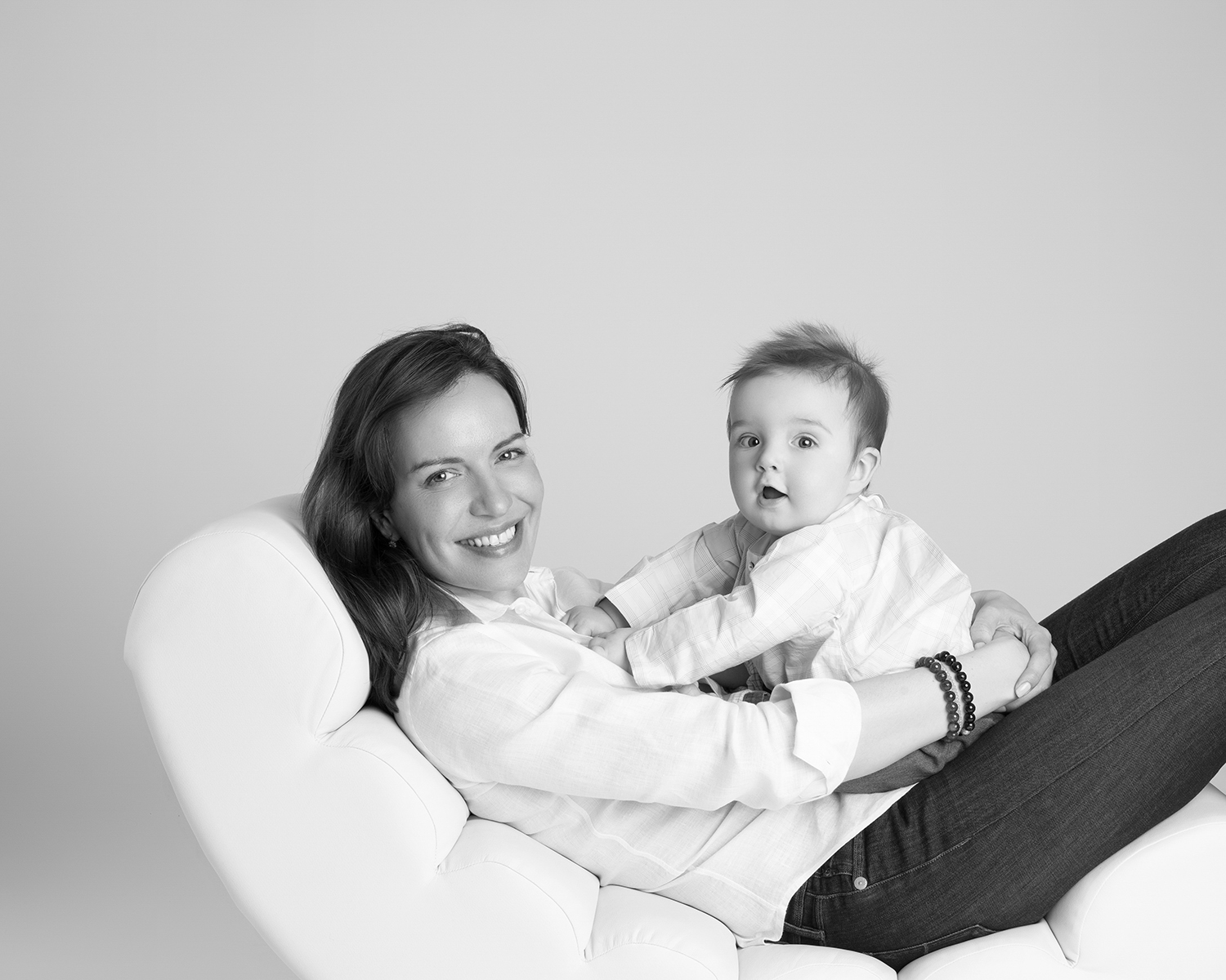 Black and white photograph of a new mum holding her baby on her lap. She is sitting on a long white reclining chair.