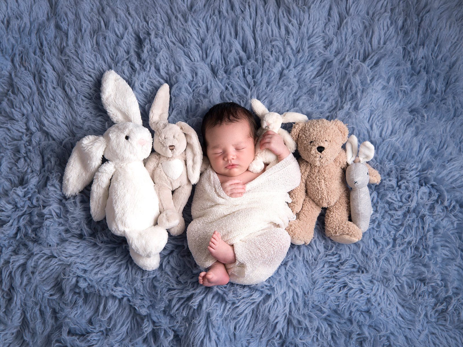Newborn baby with toys on blue rug. Image taken by award winning newborn photographer, Nemi Miller.