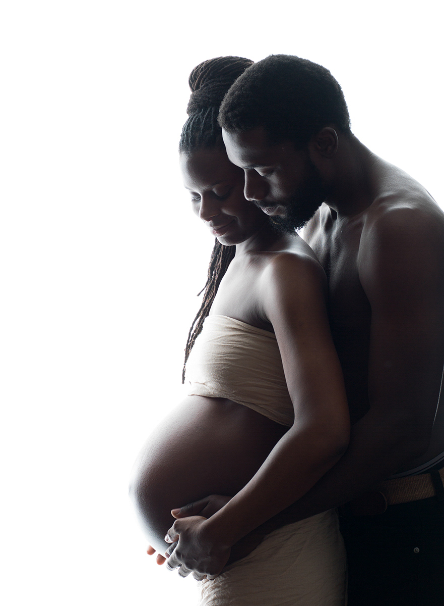 Backlit portrait of expectant parents cuddled up and holding the bump. London's top maternity photography in a studio.