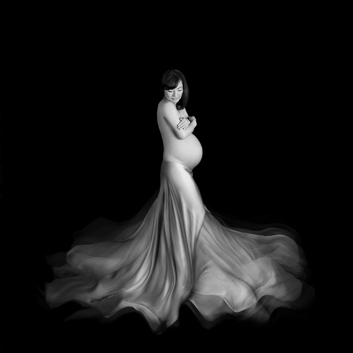 An award winning black and white maternity photograph of a pregnant woman standing up with flowing fabric.