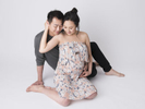 A relaxed couple's maternity photography session in a studio.