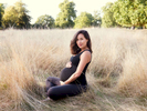 An outdoor pregnancy portrait in tall grass shot in a London park by Nemi - maternity photography specialist.