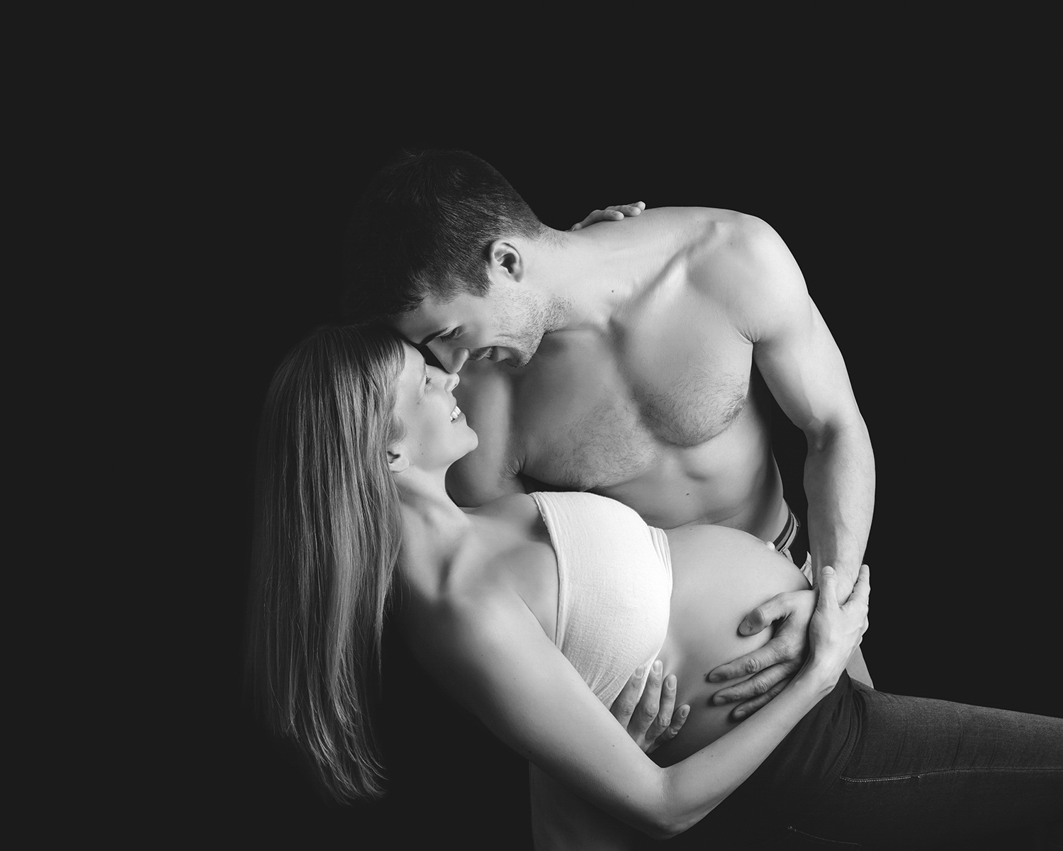 A fun black and white photograph of a man holding his expectant wife. Artistic pregnancy photography in a London studio.