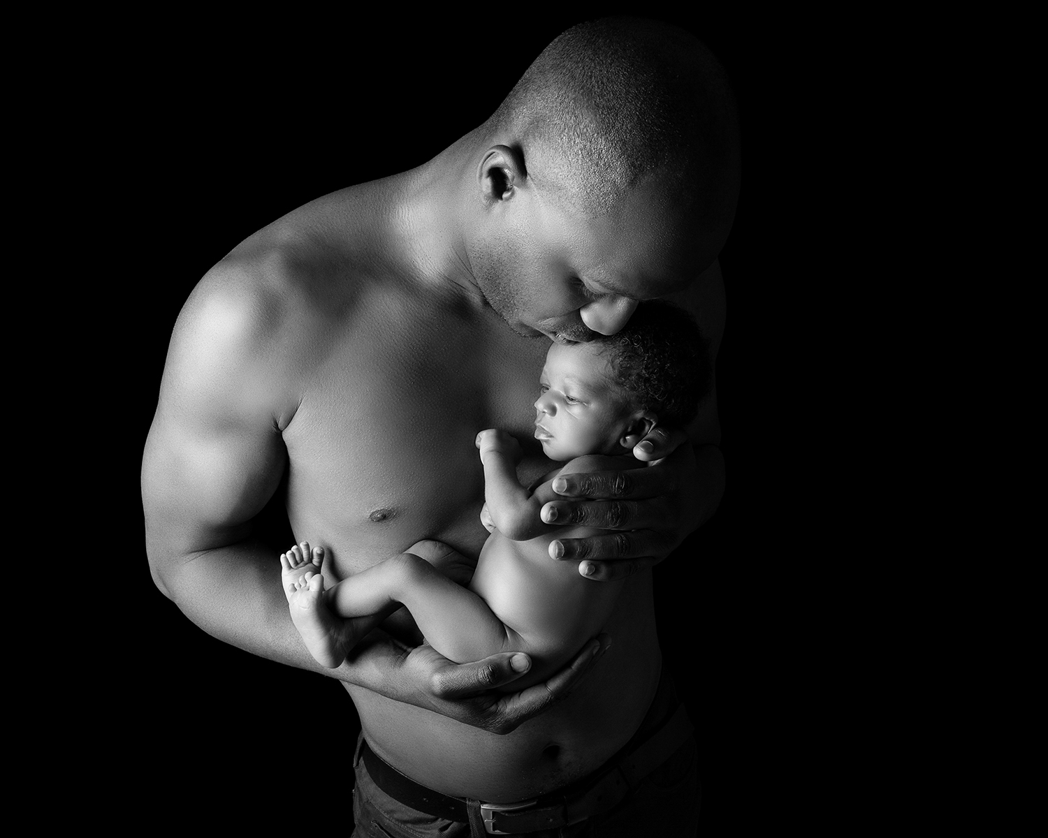Black and white photograph of a new Dad holding his baby close to his chest.