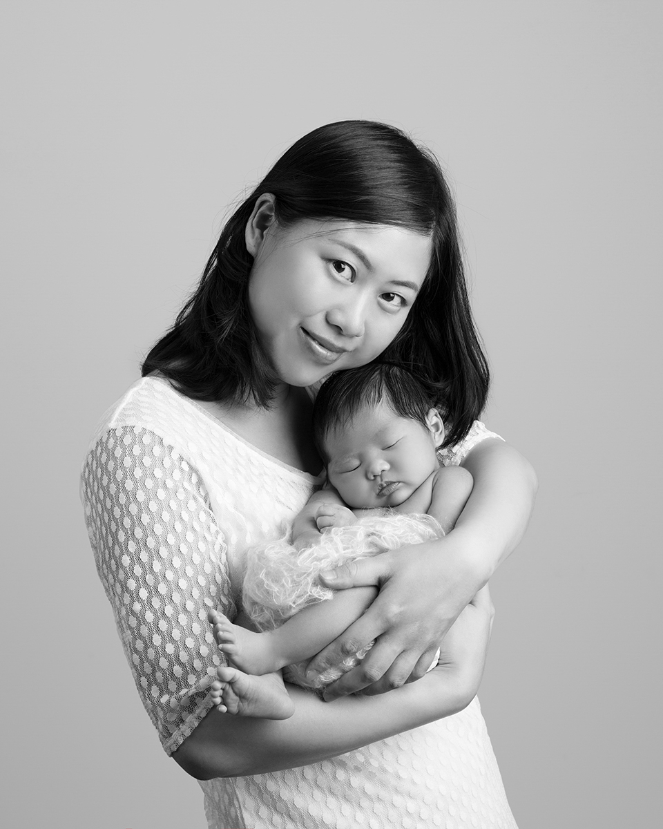 Black and white image of a mum holding her newborn baby. Photograph taken by award winning newborn photographer, Nemi Miller.