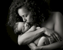 Black and white award winning newborn image 2017 of a mother holding her newborn baby in her arms.