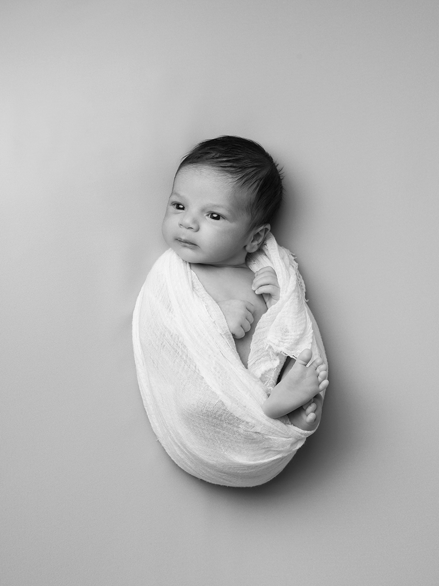 Black and white photograph of a new born baby cocooned in a white blanket.