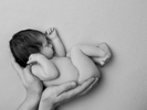 Black and white photograph of a sleeping newborn baby cuddled up and held in dad's hands. Modern newborn studio photography.