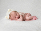 Newborn baby asleep with woolen hat. Image taken by award winning newborn photographer, Nemi Miller.