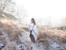 Colour maternity photograph of a pregnant woman standing in a park in winter. Nemi - award winning maternity photographer.