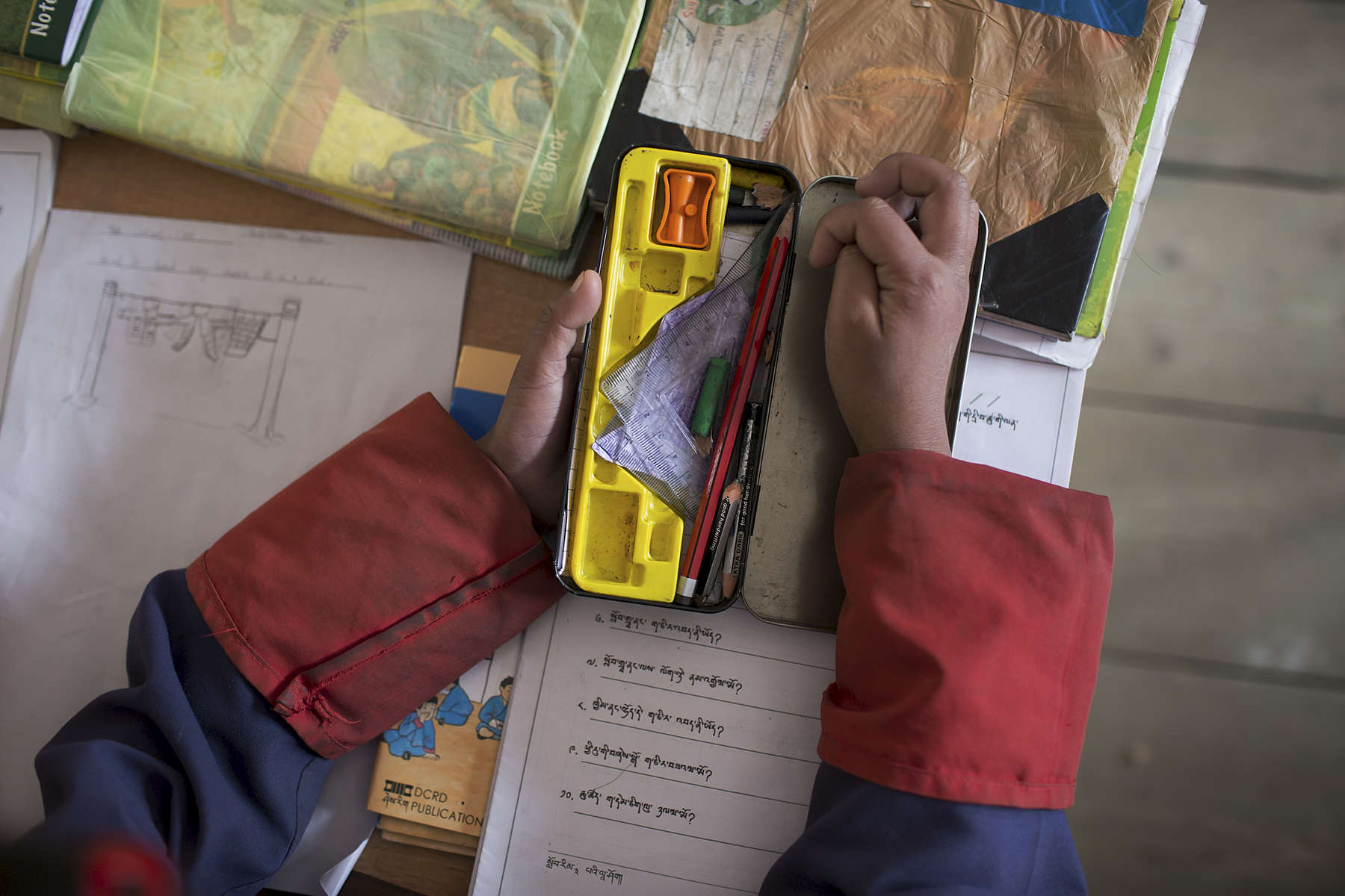 A student at Bitika Lower Secondary School takes her pencil from its case during class in Bhutan.