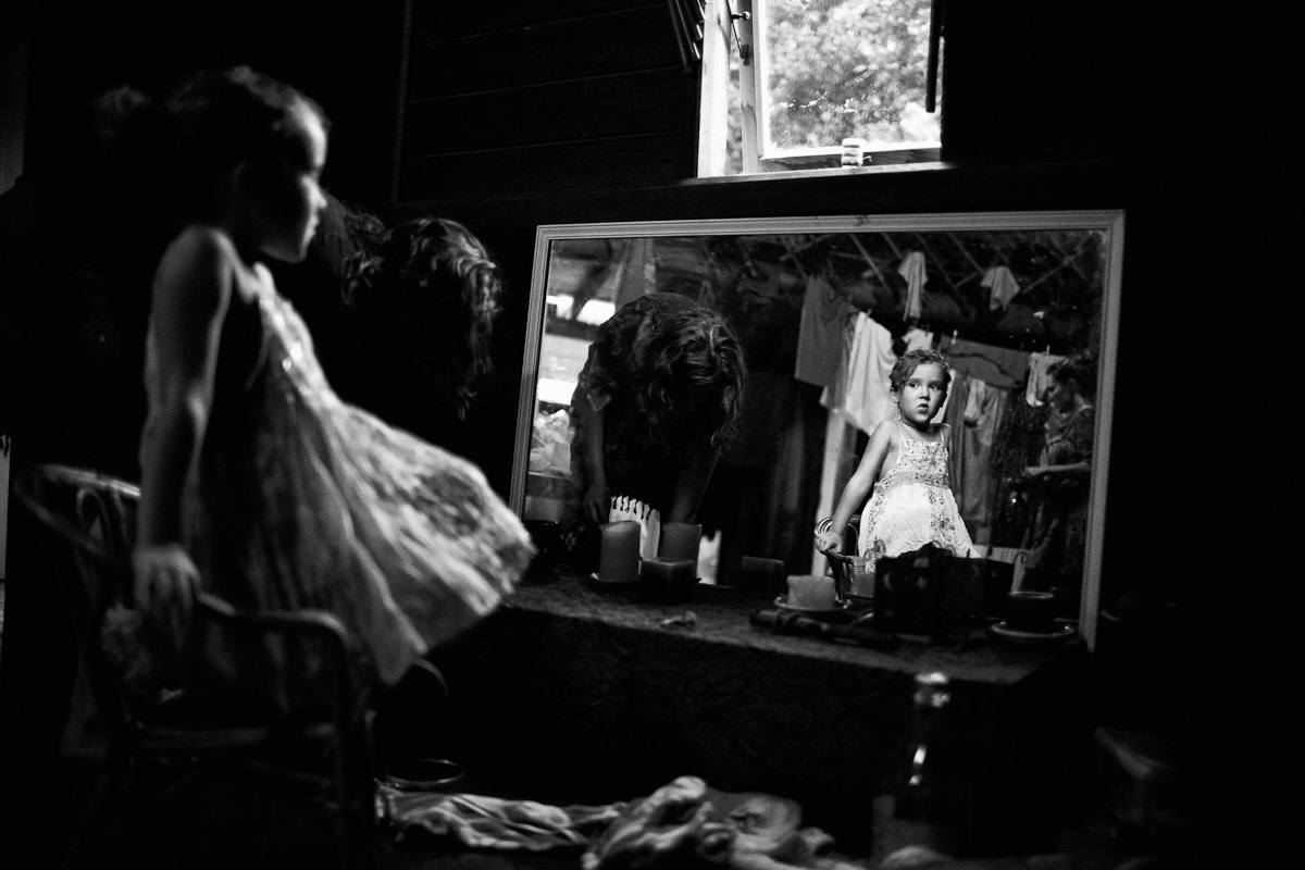 With no electricity, just the natural light available through the windows, Mali sits in front of the mirror and sings to herself.