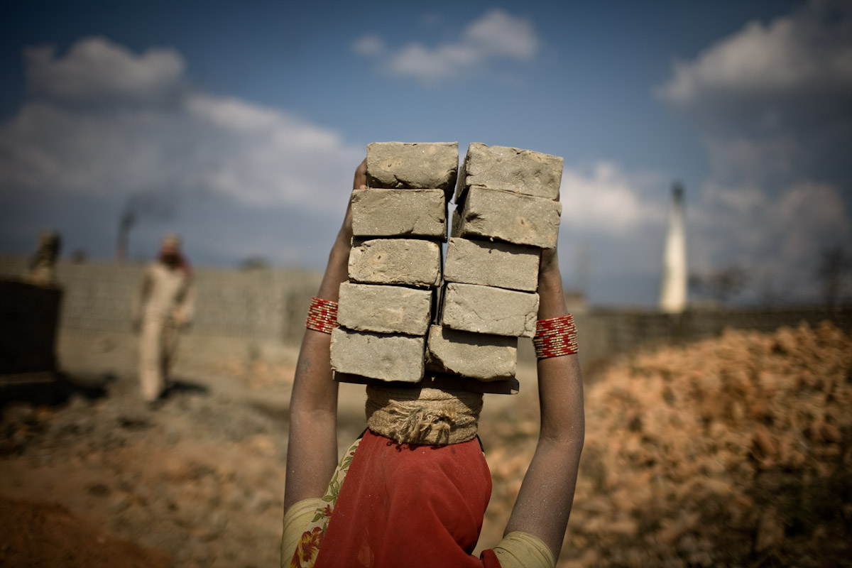 A Bihari labourer carries a load of bricks towards one of the many brick kilns in the Bhaktapur region of Nepal.