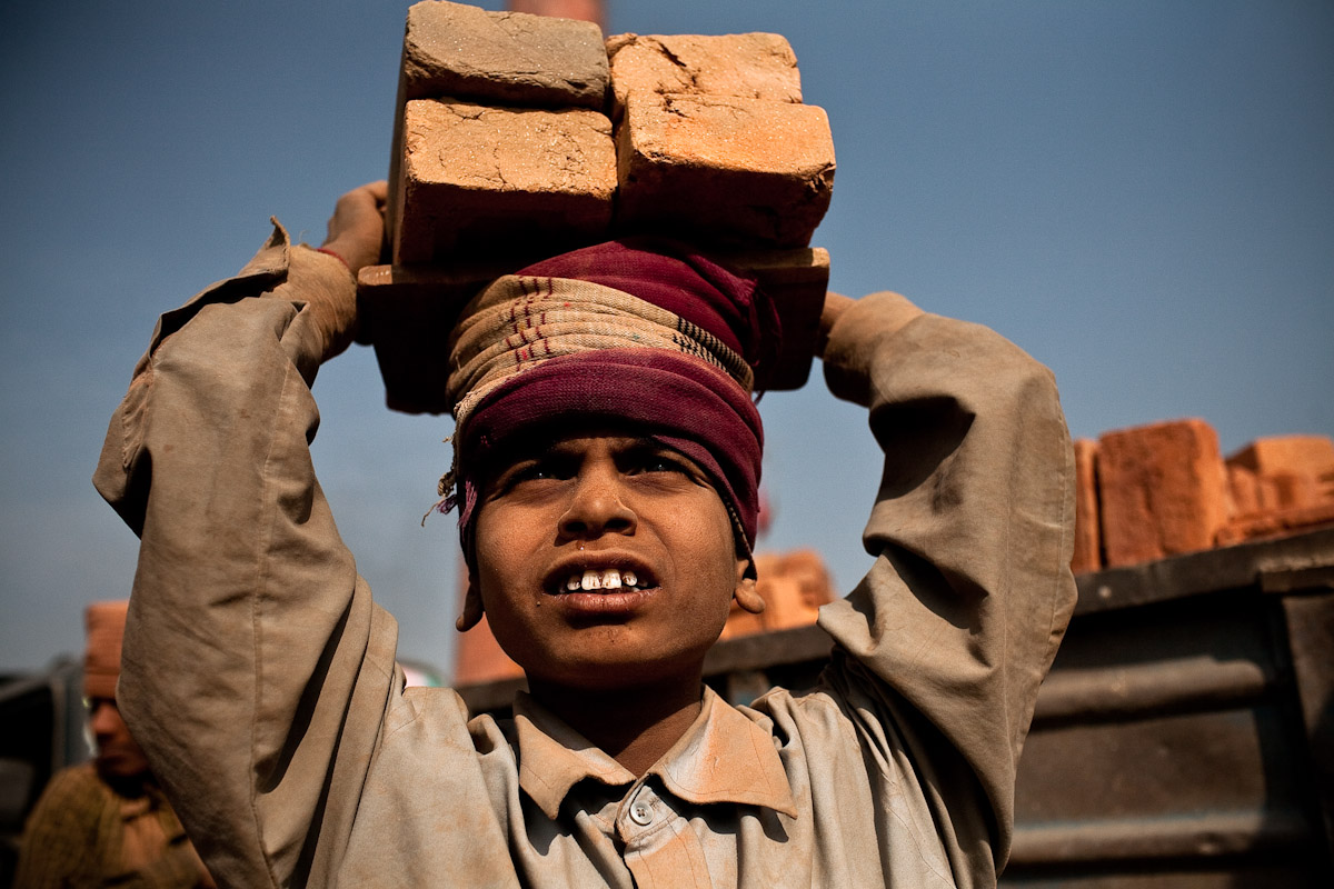 A Bihari boy carries a load of freshly baked bricks to a truck where they will travel to Kathmandu and be sold for 8 Nepali Rupees (15 US cents) each.
