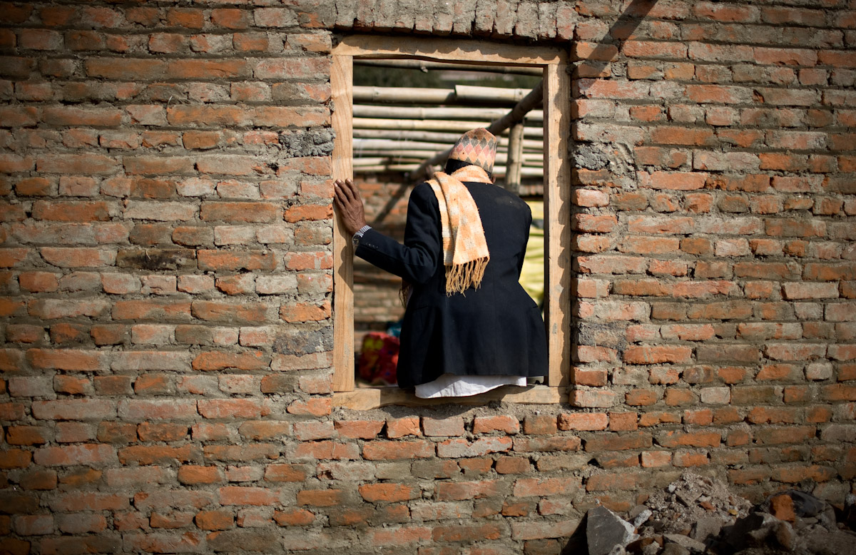 The owner of a half-constructed house sits in his window overseeing construction.