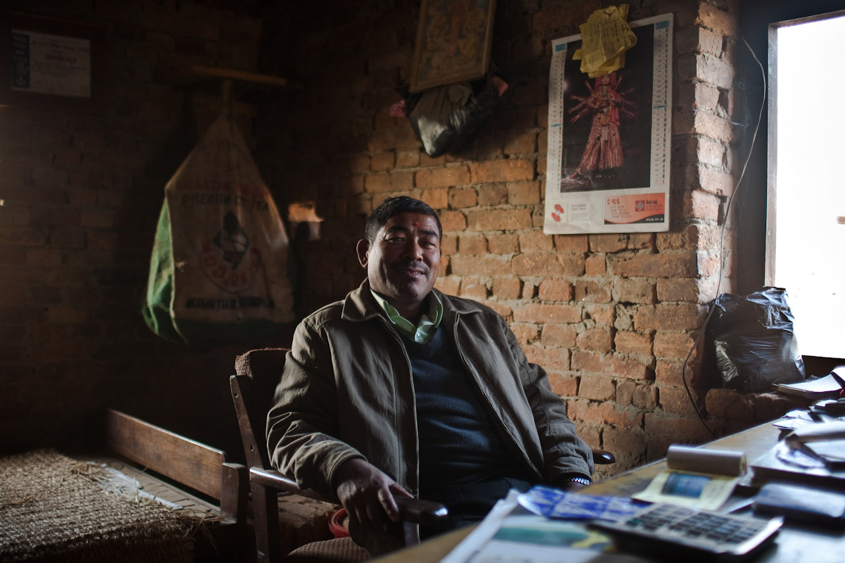 An owner of a brick kiln in Bhaktapur sits in his office, from where he can watch the workers move the bricks to and from the kiln.