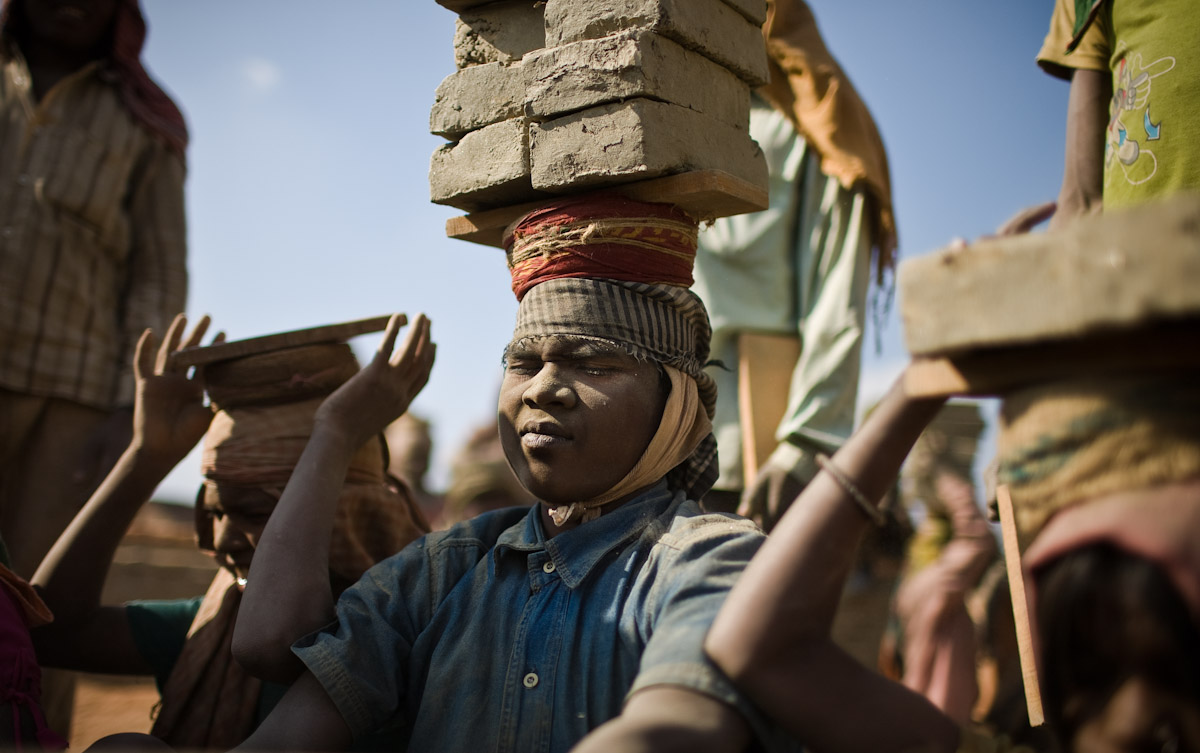 A Bihari boy collects another load of bricks from a truck to carry into the brick kiln. The bricks will cook for 15 days before they are removed and sold for 8 Nepali Rupees (10 US cents) each.
