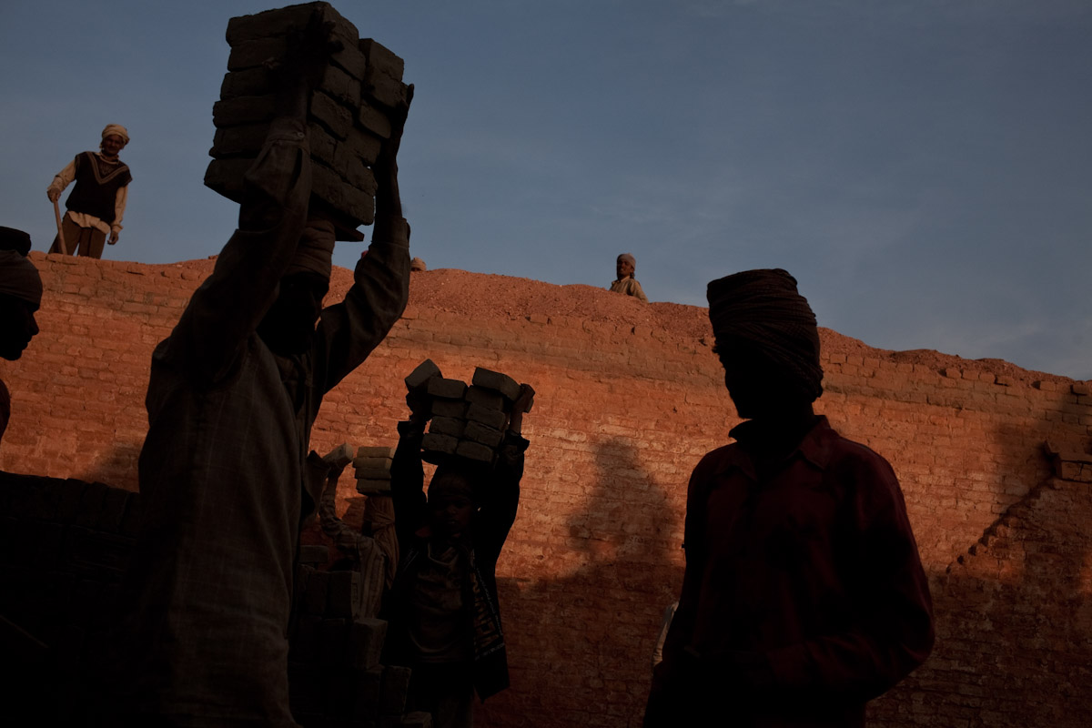 Workers continue to carry bricks into the early evening in order to entirely fill the kiln.