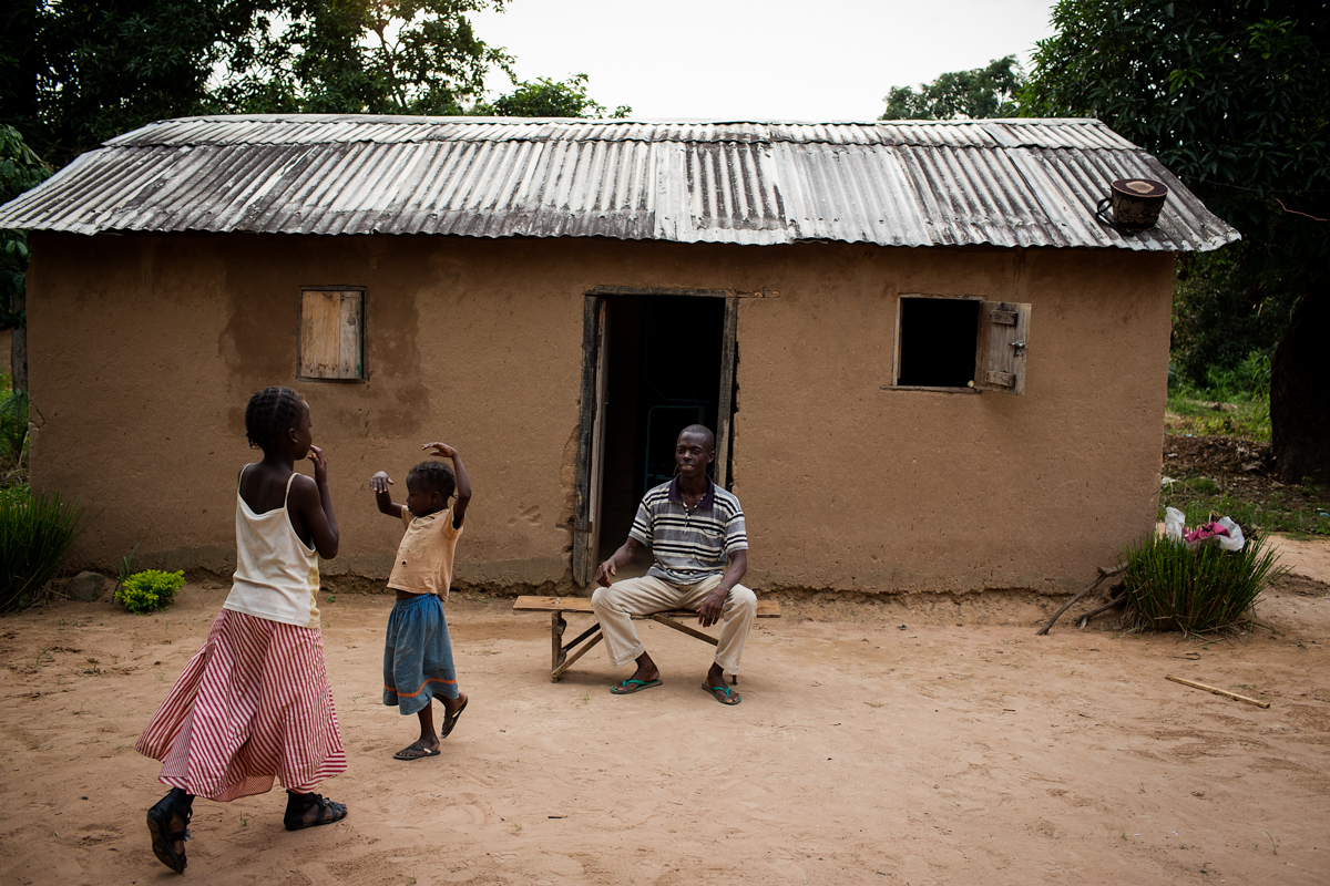 Jemimam and Monica walk towards their father Bekese Serge who sits outside his home. Bekese Serge is 40 years old and HIV positive. SOS Childrens Village provides Bekese with his Anti Retro Viral medication and also paying for his childrens school fees. Bekese's dream for the future is to buy a parcel of land he can give to his children where they can build their own home and can farm the land to grow food.