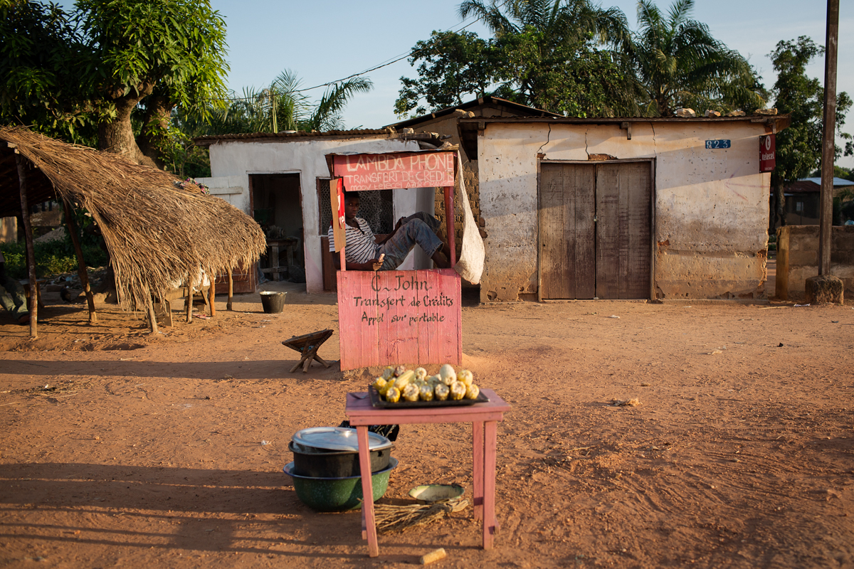 A teenage boy sits in a small booth sellling mobile phone credit. along a main road in the nieghbourhood of Bangui close to the SOS Childrens Village.