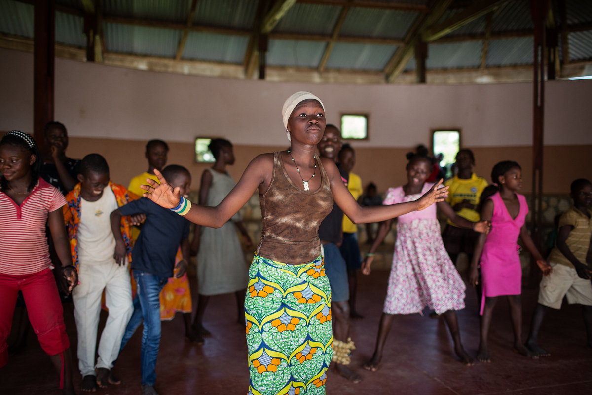 Children from the SOS Children's Village perform a traditional dance under the guidance of a dance teacher and drumming group.