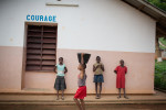 A child carries a bucket of water past Benedicte 12 years old, Mauricia 15 years old and Onela 11 years old who all live insideo House Courage at the SOS Childrens Village in Bangui.