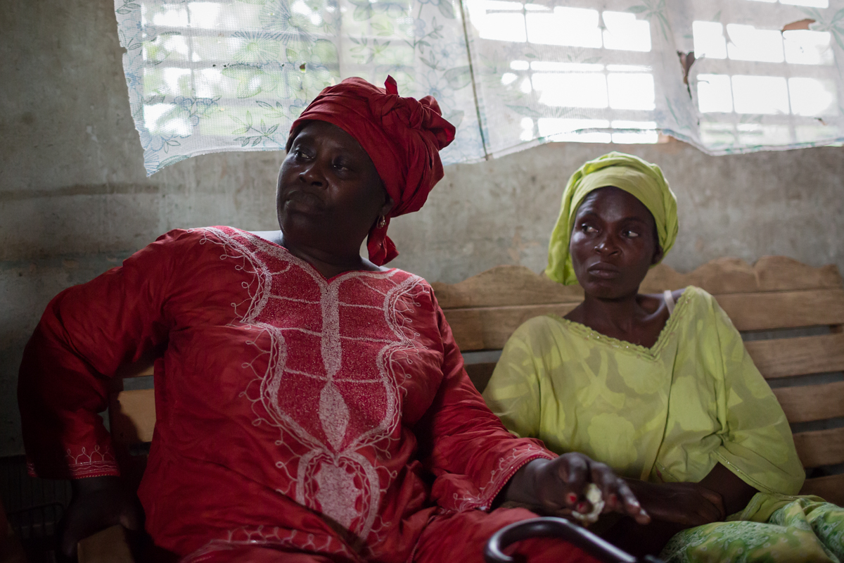 A team member of SOS Family Strengthening Program (left) sits with a member of a community HIV support group. The group was established to provide an income stream for those living with AIDS and HIV as they sell their handmade products at local markets.
