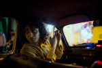 Subhankar sits inside a taxi as he travels with friends through Calcutta visiting a number of the popular Durga Puja pandals.