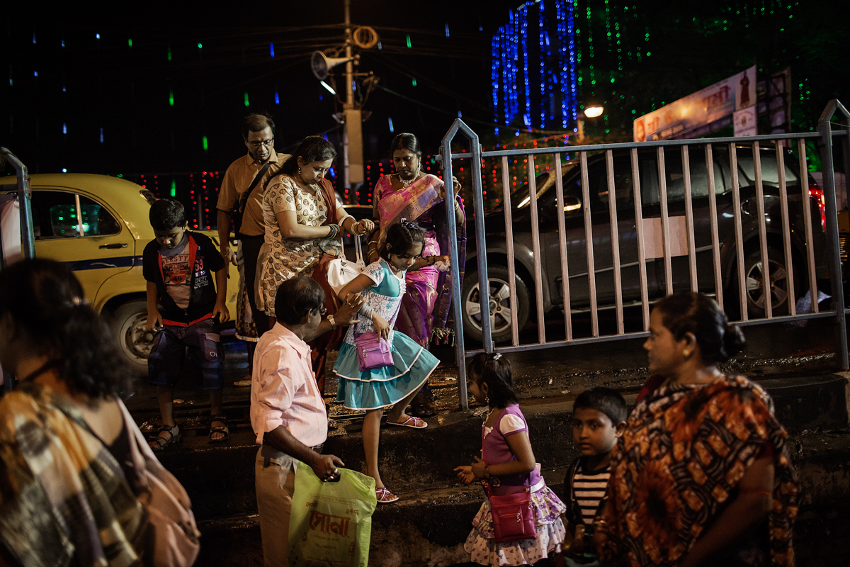 A family makes its way to the line for a popular pandal at Mohammad Ali park in central Calcutta. Pandal hopping is a favourite pastime of Bengalis during the Durga Puja festival and it includes visiting a number of the most popular pandals which can draw upwards of a 100,000 visitors a night.