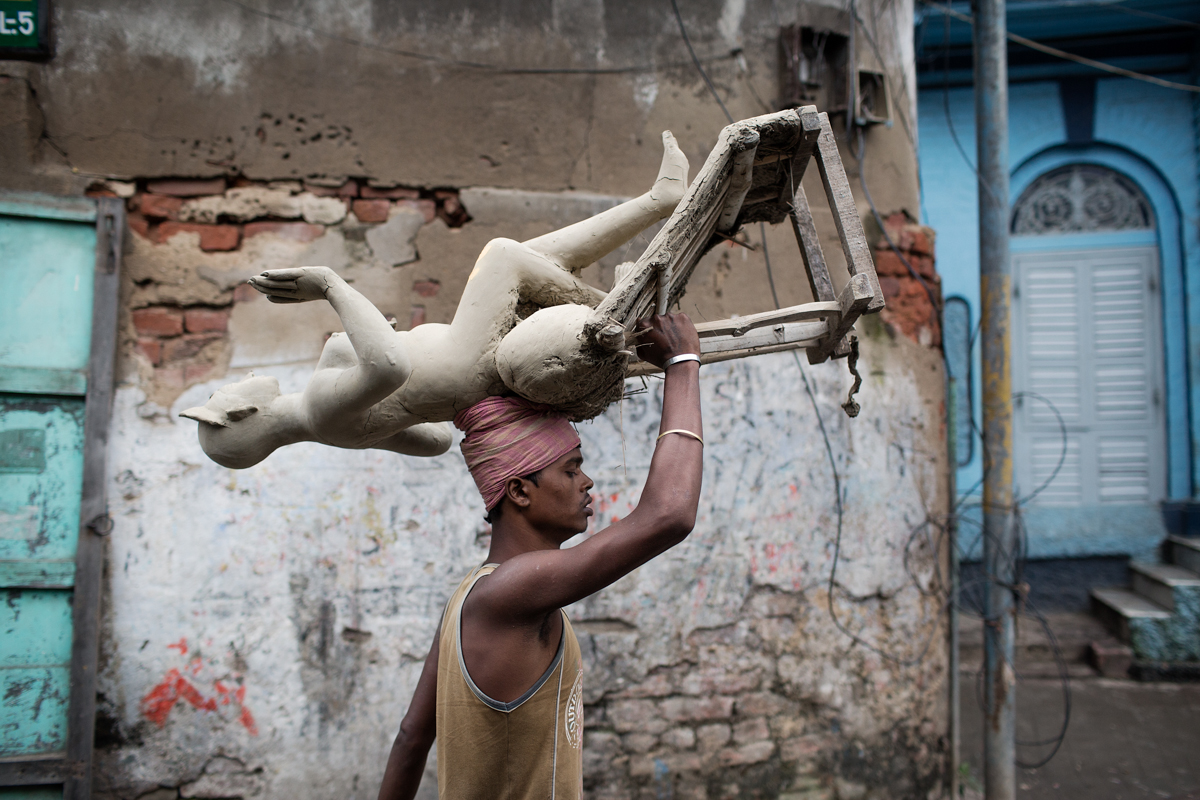 A labourer carries a clay idol through the streets of Kumortuli. Kumortuli is the artisan area of Calcutta where the Durga statues are made for the 10 day long hindu festival. Most labourers are Muslim farmers from rural West Bengal who come to the capital for the festival season.