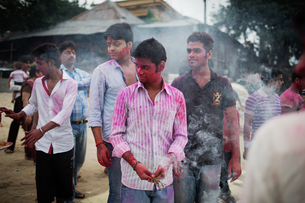 Young men light incense as they watch their family members immerse a creation  of nine plants known as Navpatrika which resembles a hunched woman in the Hooghly river.
