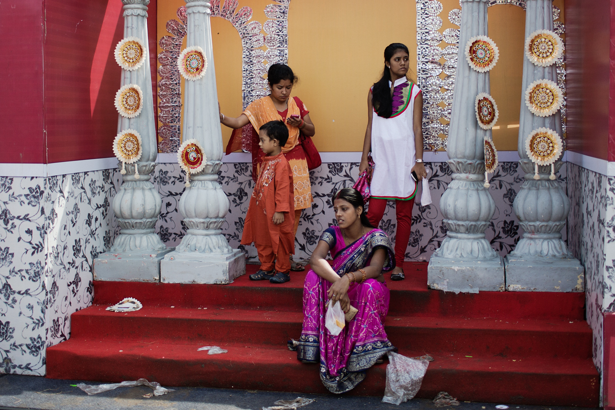A family sits down on the steps of a small stage built at the site of a popular pandal visited by thousands of people during the Durga Puja festival.