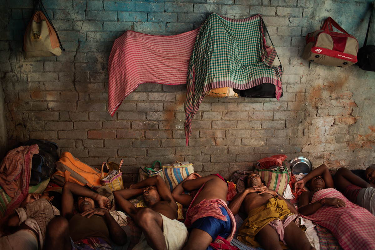 Labourers sleep in between jobs in an empty workshop in Kumortuli. Kumortuli is the artisan area of Calcutta where the Durga statues are made for the 10 day long hindu festival. Most labourers are Muslim farmers from rural West Bengal who come to the capital for the festival season.