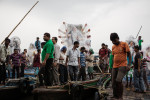 After successfully loading the large Durga statues onto their boats men from north of Calcutta prepare to set take off again.