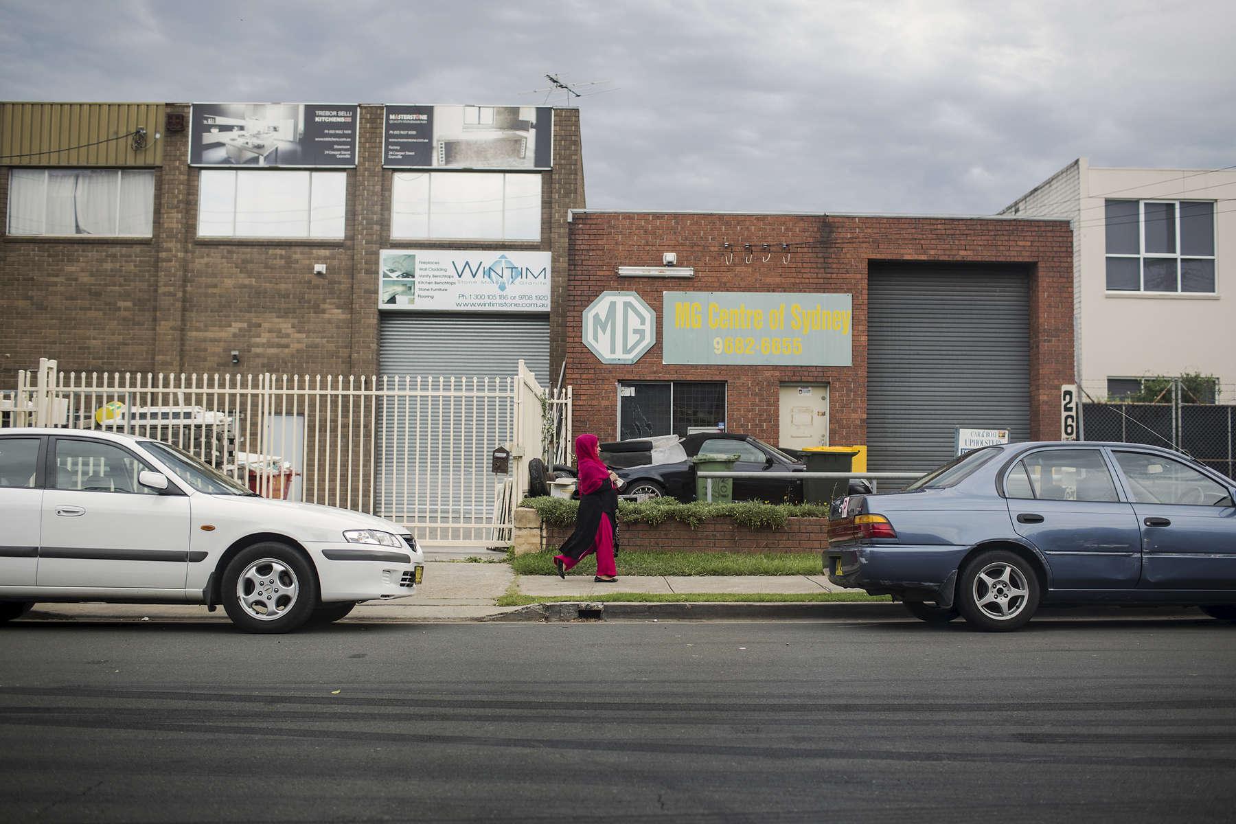 A Hazara woman walks down a street towards Shia Mosque Nabi Akram in Granville, Sydney.