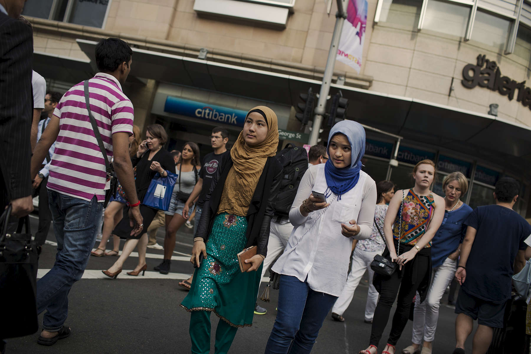 Aziza (right) and a friend cross a busy intersection in Sydney\'s CBD. Both youn women are Hazara. The Hazara are an ethnic group from Afghanistan who have been regularly targeted for their religious difference as well as  different physical appearance to the Pashtun dominated south of Afghanistan.