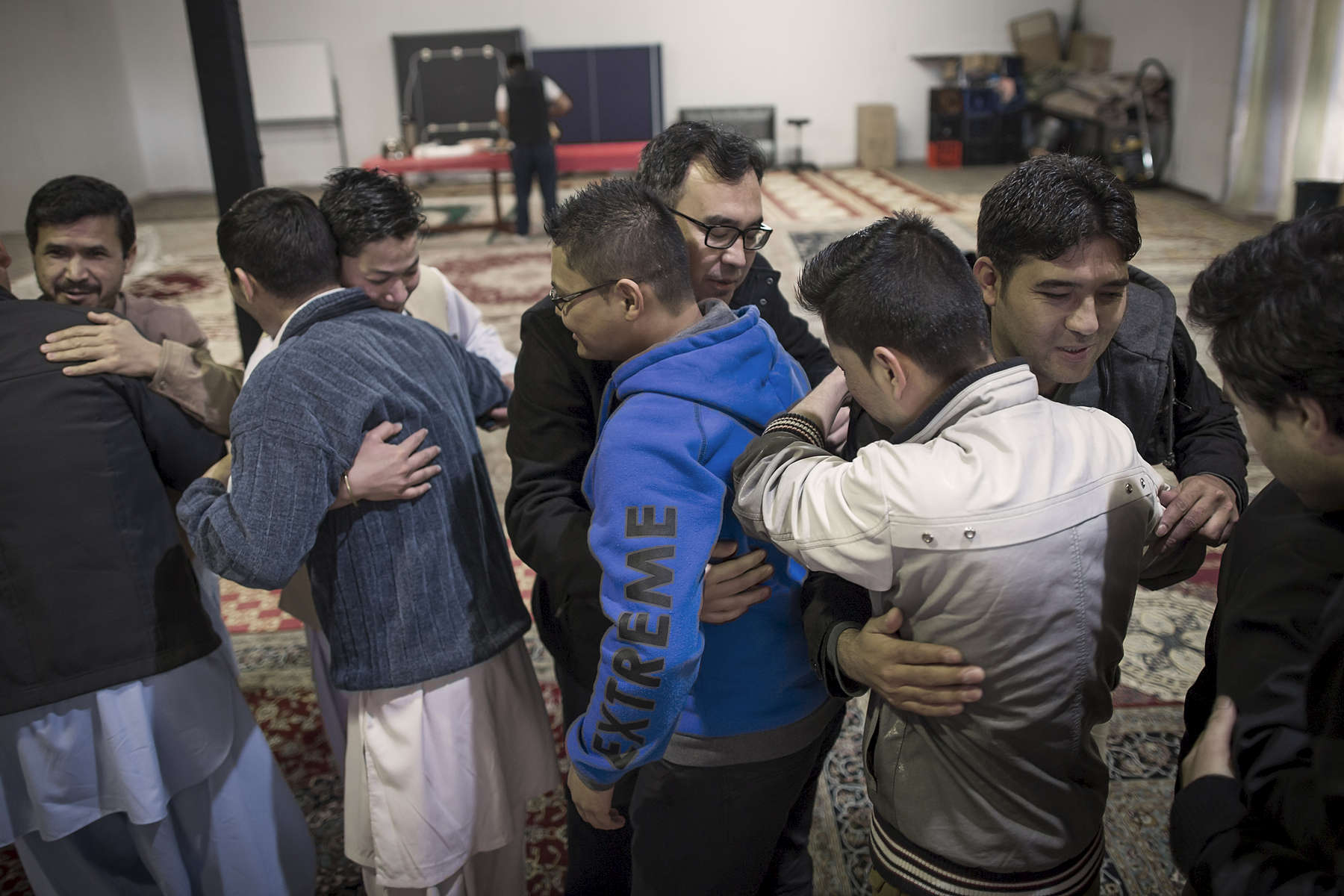 At the Imam Ali Centre in Kemps Creek in Greater Sydney members of the Hazara community embrace each other after the Eid Al-Fitr prayers which marks the end of the holy month of Ramadan. The community at Imam Ali Centre are Hazaras who have grown up in Quetta, Pakistan. Many members find it easier to understand their own Sheikhs sermons and lectures as they\'ve similarly lived  in Quetta and speak Dari with the same accent.