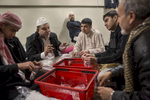 A group of young men and elders sit together talking as they pack small bags of sweets to be given out during Iftar meal at the Blacktown Mosque. The Blacktown Mosque is Sunni with most of the community from the Pashtun and Tajik communities in Afghanistan.