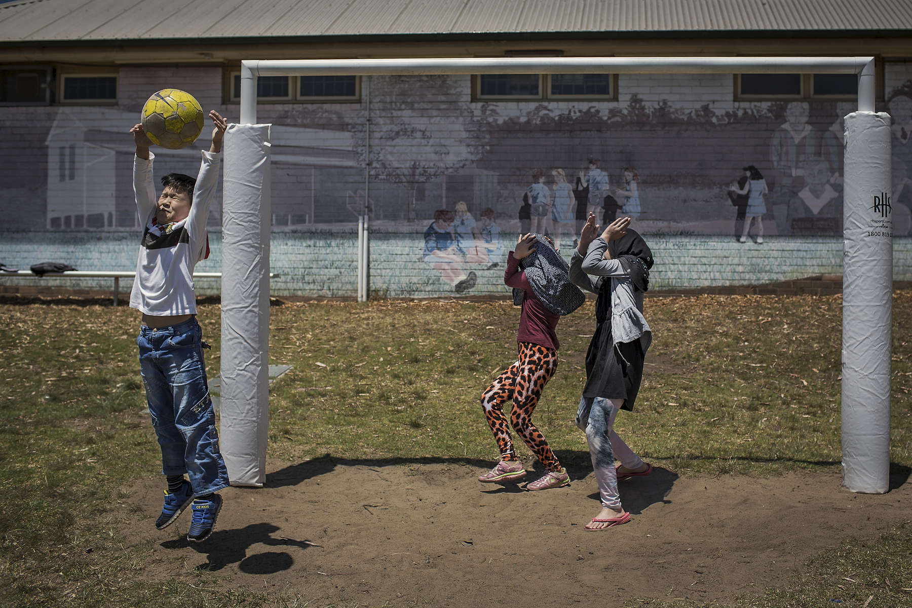 A young Afghan boy saves a goal kick as two girls hide from the oncoming ball. The children all attend the Kateb Hazara Association weekend school in Sydney where they learn to read and write in Dari and Hazaragi while also learning to recite from the Quran.