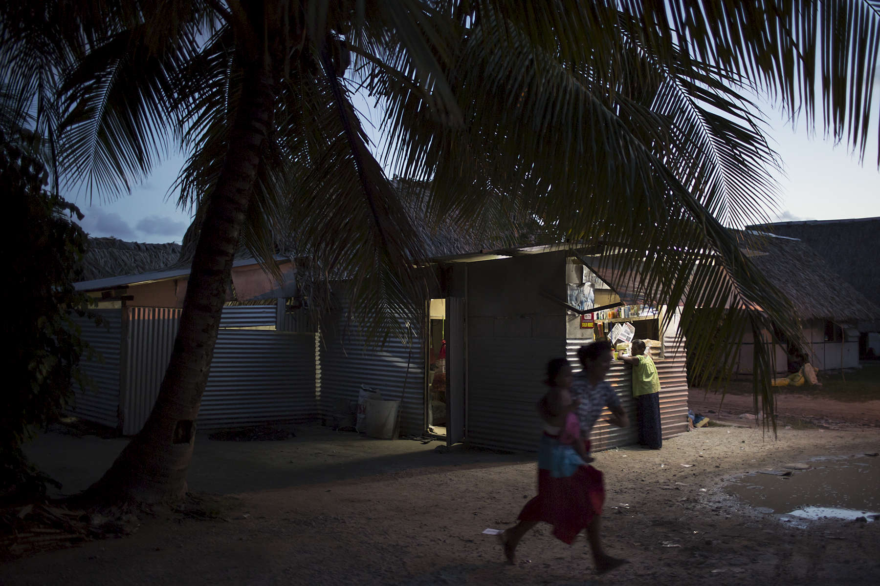 At dusk after a domestic dispute a woman runs from her house carrying a young child. Domestic violence is a big social issue in Kiribati. During the photographers stay in 2014, two women were murdered by their partners in domestic disputes.