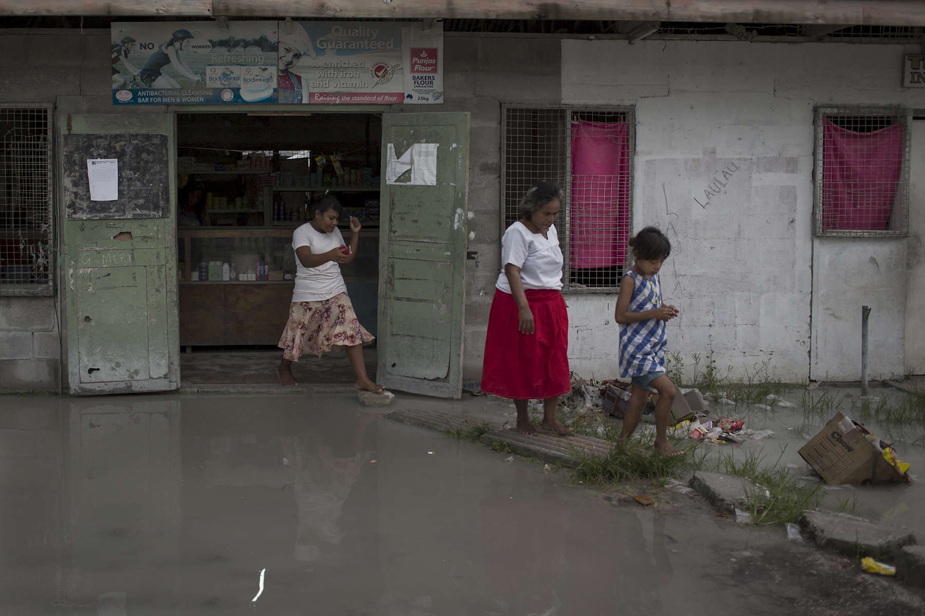 Women and a young girl leave a shop which experienced flash flooding around the outside of the shop after an early morning downpour.