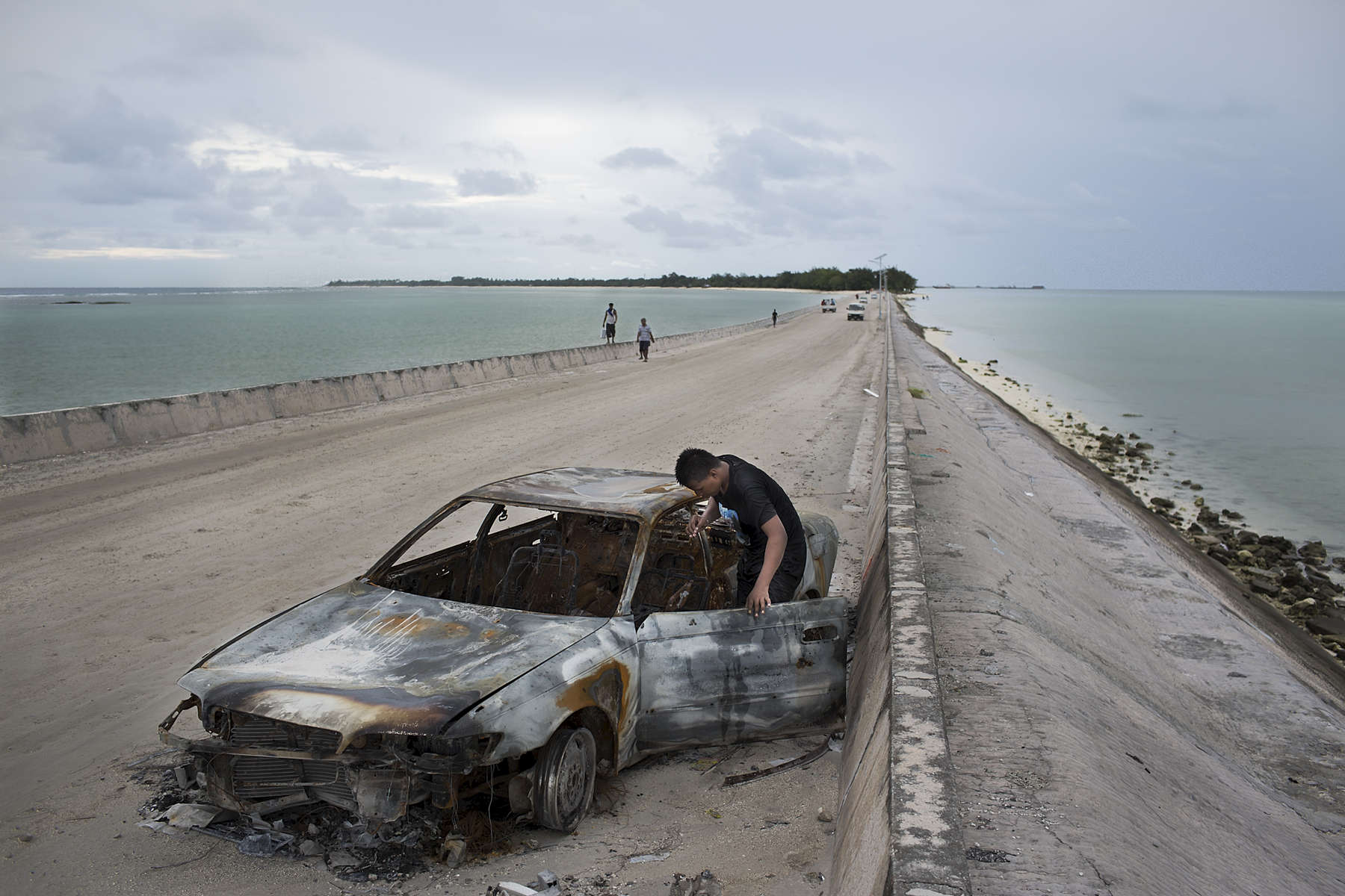 A young man inspects a burnt out car along the Betio and Bairiki Causeway, South Tarawa. Betio is the most densely populated villages in Kiribati, while Bairiki is the adminastritive capital of the small pacific nation.